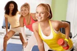 Fit girl exercising with dumbbells smiling