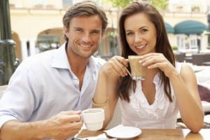 Young Couple Enjoying Coffee And Cake In Caf